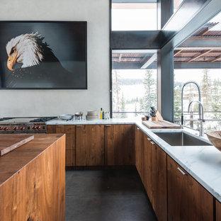 Cette image montre une grand cuisine américaine chalet en L avec un évier encastré, un placard à porte plane, béton au sol, un îlot central, des portes de placard en bois brun, un plan de travail en marbre et un électroménager en acier inoxydable.