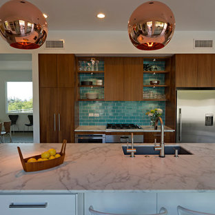This is an example of a midcentury open plan kitchen in Phoenix with an undermount sink, flat-panel cabinets, medium wood cabinets, marble benchtops, blue splashback, ceramic splashback, stainless steel appliances, porcelain floors and with island.