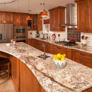 Bild på ett mellanstort vintage kök, med en undermonterad diskho, luckor med upphöjd panel, skåp i mellenmörkt trä, granitbänkskiva, vitt stänkskydd, stänkskydd i tunnelbanekakel, rostfria vitvaror, klinkergolv i porslin och en köksö