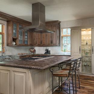 Immagine di una grande cucina stile rurale con ante di vetro, ante con finitura invecchiata, top in quarzite, paraspruzzi beige, paraspruzzi con piastrelle in ceramica, elettrodomestici in acciaio inossidabile, parquet scuro, isola, pavimento marrone e lavello stile country