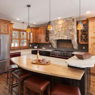 デンバーのラスティックスタイルのおしゃれなキッチン (ダブルシンク、落し込みパネル扉のキャビネット、中間色木目調キャビネット、グレーのキッチンパネル、シルバーの調理設備の、無垢フローリング、茶色い床、白いキッチンカウンター) の写真