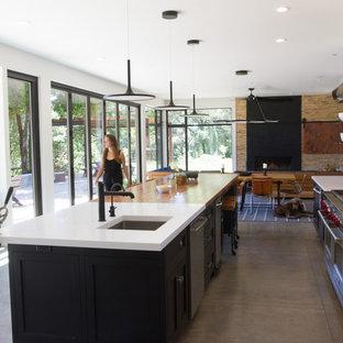 サンフランシスコのラスティックスタイルのおしゃれなキッチン (黒いキャビネット、木材カウンター、白いキッチンパネル、シルバーの調理設備の、コンクリートの床、グレーの床、白いキッチンカウンター、アンダーカウンターシンク、シェーカースタイル扉のキャビネット) の写真
