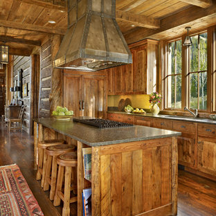 Immagine di una cucina abitabile stile rurale di medie dimensioni con ante in legno scuro, top in granito, pavimento in legno massello medio, ante con bugna sagomata, paraspruzzi in mattoni e isola