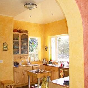 Geschlossene, Kleine Mediterrane Küche in U-Form mit Unterbauwaschbecken, Schrankfronten mit vertiefter Füllung, hellen Holzschränken, Granit-Arbeitsplatte, Küchengeräten aus Edelstahl, Betonboden, Kücheninsel, grauem Boden, Küchenrückwand in Gelb und brauner Arbeitsplatte in San Francisco