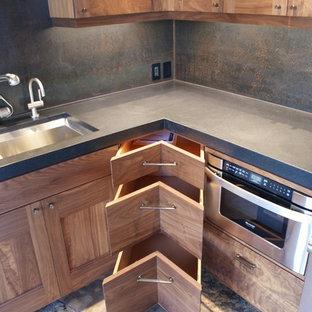 デンバーの中くらいのおしゃれなキッチン (黒いキッチンパネル、ダブルシンク、シェーカースタイル扉のキャビネット、濃色木目調キャビネット、コンクリートカウンター、石スラブのキッチンパネル、シルバーの調理設備、スレートの床、アイランドなし) の写真