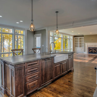 Expansive transitional l-shaped open plan kitchen in New York with a farmhouse sink, raised-panel cabinets, beige cabinets, soapstone benchtops, beige splashback, porcelain splashback, panelled appliances, dark hardwood floors and with island.