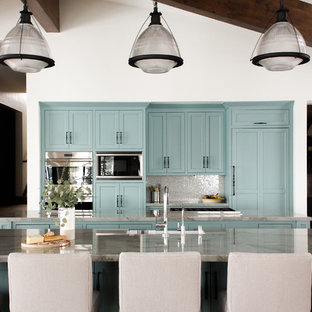 Inredning av ett rustikt grå grått kök, med en undermonterad diskho, skåp i shakerstil, gröna skåp, stänkskydd med metallisk yta, rostfria vitvaror och en köksö