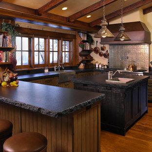 ボイシの大きいラスティックスタイルのおしゃれなキッチン (エプロンフロントシンク、シルバーの調理設備の、シェーカースタイル扉のキャビネット、ソープストーンカウンター、グレーのキッチンパネル、濃色木目調キャビネット、濃色無垢フローリング) の写真