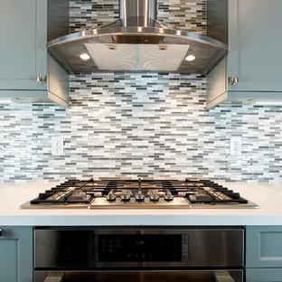サンフランシスコの広いコンテンポラリースタイルのおしゃれなキッチン (グレーのキャビネット、マルチカラーのキッチンパネル、シルバーの調理設備、ドロップインシンク、インセット扉のキャビネット、御影石カウンター、ボーダータイルのキッチンパネル、無垢フローリング、茶色い床、白いキッチンカウンター) の写真