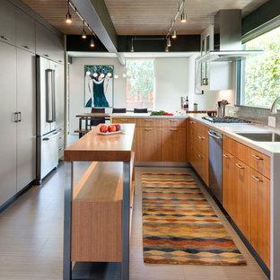 На фото: большая параллельная кухня в современном стиле с обеденным столом, одинарной раковиной, плоскими фасадами, техникой из нержавеющей стали, островом, светлыми деревянными фасадами, столешницей из акрилового камня, серым фартуком, фартуком из плитки мозаики, полом из ламината и коричневым полом