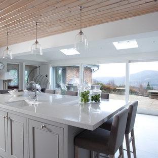 Ejemplo de cocina en U, de estilo de casa de campo, grande, abierta, con armarios estilo shaker, puertas de armario grises, encimera de mármol y península
