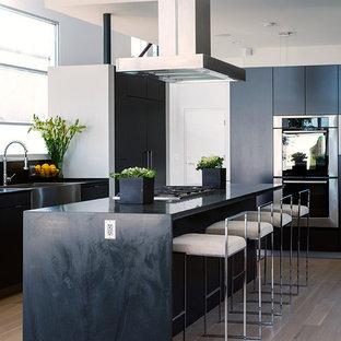 Inspiration för stora moderna svart kök, med en rustik diskho, släta luckor, svarta skåp, rostfria vitvaror, ljust trägolv, en köksö, träbänkskiva, fönster som stänkskydd och beiget golv