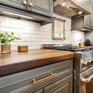 Einzeilige, Mittelgroße Klassische Wohnküche mit Unterbauwaschbecken, profilierten Schrankfronten, grauen Schränken, Betonarbeitsplatte, Küchenrückwand in Weiß, Rückwand aus Metrofliesen, Küchengeräten aus Edelstahl, braunem Holzboden, Kücheninsel, braunem Boden und bunter Arbeitsplatte in New York