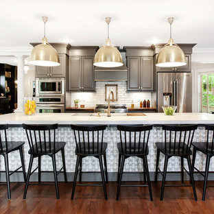 Transitional open concept kitchen ideas - Transitional galley dark wood floor and brown floor open concept kitchen photo in New York with raised-panel cabinets, gray cabinets, white backsplash, stainless steel appliances, an island and white countertops