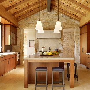 Photo of a country galley kitchen in San Francisco with an undermount sink, flat-panel cabinets, medium wood cabinets, limestone benchtops, panelled appliances, limestone floors, with island, beige floor and limestone splashback.