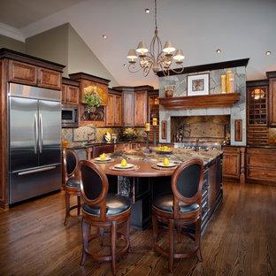 Mittelgroße, Offene Urige Küche in U-Form mit Landhausspüle, profilierten Schrankfronten, dunklen Holzschränken, bunter Rückwand, Küchengeräten aus Edelstahl, dunklem Holzboden, Kücheninsel, Rückwand aus Schiefer, Granit-Arbeitsplatte und braunem Boden in Sonstige
