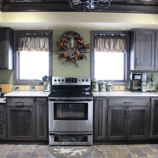 Mid-sized country u-shaped eat-in kitchen in Philadelphia with a farmhouse sink, shaker cabinets, dark wood cabinets, quartz benchtops, orange splashback, ceramic splashback, stainless steel appliances, laminate floors, a peninsula, multi-coloured floor and beige benchtop.