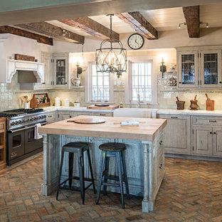 Inspiration för avskilda, mellanstora lantliga u-kök, med en rustik diskho, luckor med upphöjd panel, skåp i slitet trä, marmorbänkskiva, beige stänkskydd, stänkskydd i keramik, integrerade vitvaror, tegelgolv och en köksö