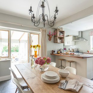 This is an example of a medium sized traditional u-shaped kitchen/diner in Other with shaker cabinets, white cabinets, grey splashback, metro tiled splashback, a breakfast bar, grey floors, wood worktops and slate flooring.