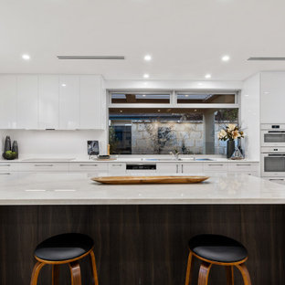 Inspiration for a large contemporary u-shaped kitchen in Perth with a double-bowl sink, flat-panel cabinets, white cabinets, white splashback, medium hardwood floors, with island, beige floor and white benchtop.