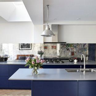 Ejemplo de cocina ecléctica, de tamaño medio, abierta, con fregadero bajoencimera, armarios con paneles lisos, puertas de armario azules, encimera de cuarcita, salpicadero metalizado, salpicadero de vidrio templado, electrodomésticos de acero inoxidable y suelo de madera en tonos medios