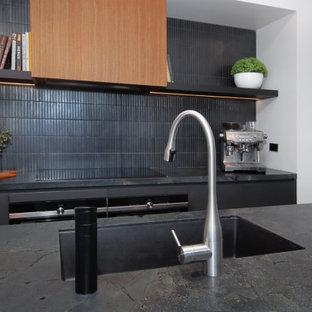 Exempel på ett mellanstort modernt svart svart kök, med en dubbel diskho, släta luckor, bruna skåp, granitbänkskiva, svart stänkskydd, stänkskydd i keramik, svarta vitvaror, cementgolv, en köksö och beiget golv