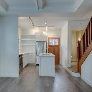 Inspiration for a mid-sized arts and crafts galley eat-in kitchen in Vancouver with a double-bowl sink, flat-panel cabinets, white cabinets, quartzite benchtops, white splashback, stainless steel appliances, light hardwood floors and with island.