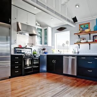 Contemporary kitchen inspiration - Trendy l-shaped kitchen photo in Orange County with black appliances, black cabinets, flat-panel cabinets, white backsplash, subway tile backsplash and quartz countertops