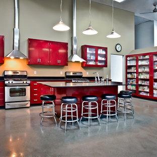 Industrial Küche in L-Form mit Küchengeräten aus Edelstahl, roten Schränken und flächenbündigen Schrankfronten in Orange County