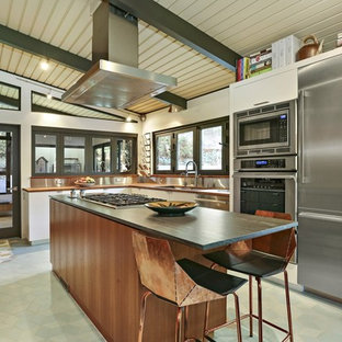 Midcentury u-shaped kitchen in Los Angeles with an undermount sink, flat-panel cabinets, medium wood cabinets, grey splashback, metal splashback, stainless steel appliances, with island, green floor and black benchtop.