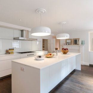 Contemporary galley kitchen in Surrey with flat-panel cabinets, white cabinets, white splashback, dark hardwood flooring, an island, brown floors and white worktops.