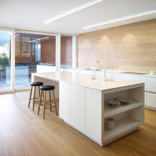 Idee per una cucina parallela contemporanea con ante lisce, ante bianche, parquet chiaro, isola e paraspruzzi marrone
