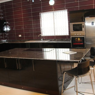 Inspiration for a mid-sized modern l-shaped ceramic floor open concept kitchen remodel in Other with a double-bowl sink, flat-panel cabinets, black cabinets, granite countertops, gray backsplash, stone slab backsplash, stainless steel appliances and an island