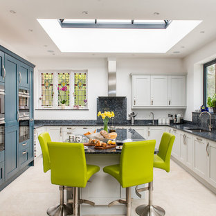 Inspiration for a medium sized classic u-shaped kitchen/diner in Surrey with recessed-panel cabinets, blue cabinets, granite worktops, integrated appliances, ceramic flooring, an island, beige floors, a submerged sink and grey worktops.
