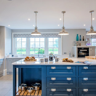 Large traditional open plan kitchen in Surrey with shaker cabinets, blue cabinets, quartz worktops, white splashback, stainless steel appliances, porcelain flooring, an island and grey floors.