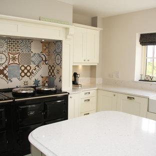他の地域の大きいコンテンポラリースタイルのおしゃれなキッチン (ドロップインシンク、フラットパネル扉のキャビネット、白いキャビネット、御影石カウンター、パネルと同色の調理設備、セラミックタイルの床) の写真