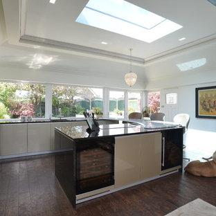 マンチェスターのモダンスタイルのおしゃれなアイランドキッチン (ドロップインシンク、フラットパネル扉のキャビネット、ベージュのキャビネット、御影石カウンター、カラー調理設備、クッションフロア) の写真