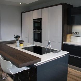 Modern inredning av ett mellanstort kök, med en nedsänkt diskho, släta luckor, svarta skåp, granitbänkskiva, integrerade vitvaror, mellanmörkt trägolv och en köksö