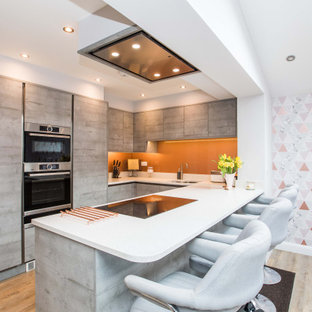 Inspiration for a contemporary u-shaped kitchen in West Midlands with a submerged sink, flat-panel cabinets, light wood cabinets, orange splashback, integrated appliances, light hardwood flooring, a breakfast bar, brown floors and white worktops.