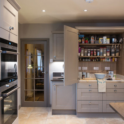 Example of a transitional kitchen design in Surrey with shaker cabinets, gray cabinets, stainless steel appliances and an island