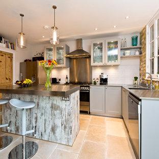 Foto på ett mellanstort vintage l-kök, med bänkskiva i rostfritt stål, en köksö, beiget golv, stänkskydd med metallisk yta, stänkskydd i metallkakel, en integrerad diskho, skåp i shakerstil, grå skåp och rostfria vitvaror