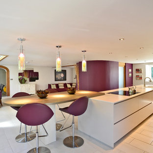 Contemporary eat-in kitchen inspiration - Example of a trendy galley eat-in kitchen design in Manchester with flat-panel cabinets, white cabinets and wood countertops