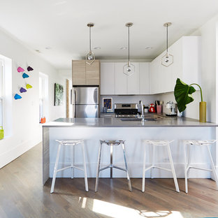 Inspiration for a large eclectic u-shaped open plan kitchen in Chicago with medium hardwood floors, an undermount sink, flat-panel cabinets, granite benchtops, stainless steel appliances, white cabinets and a peninsula.
