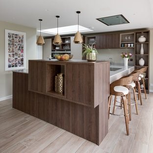 Large contemporary u-shaped kitchen/diner in Buckinghamshire with a submerged sink, flat-panel cabinets, beige cabinets, quartz worktops, integrated appliances and ceramic flooring.