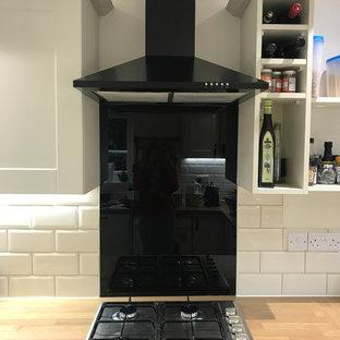 他の地域の中サイズのシャビーシック調のおしゃれなキッチン (シングルシンク、シェーカースタイル扉のキャビネット、白いキャビネット、ラミネートカウンター、黒いキッチンパネル、ガラス板のキッチンパネル、黒い調理設備、クッションフロア、アイランドなし、グレーの床) の写真