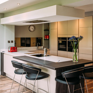 Small contemporary u-shaped eat-in kitchen in Other with mirror splashback, an undermount sink, flat-panel cabinets, white cabinets, limestone benchtops, panelled appliances, medium hardwood floors, a peninsula and brown floor.