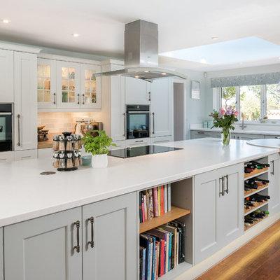 Kitchen - transitional medium tone wood floor kitchen idea in Other with shaker cabinets, gray cabinets, multicolored backsplash, subway tile backsplash, black appliances and an island
