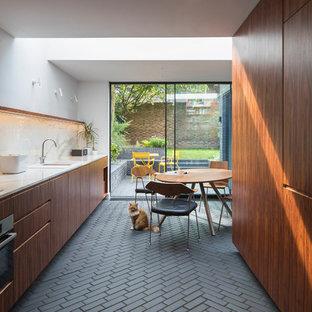 Inredning av ett modernt kök, med släta luckor, skåp i mörkt trä, marmorbänkskiva, vitt stänkskydd, stänkskydd i marmor, tegelgolv och svart golv