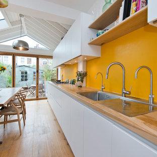 ロンドンの中サイズのコンテンポラリースタイルのおしゃれなダイニングキッチン (ダブルシンク、フラットパネル扉のキャビネット、白いキャビネット、木材カウンター、カラー調理設備、無垢フローリング、アイランドなし、ベージュの床) の写真