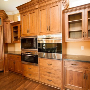 Large craftsman eat-in kitchen appliance - Eat-in kitchen - large craftsman u-shaped medium tone wood floor eat-in kitchen idea in Philadelphia with a double-bowl sink, raised-panel cabinets, medium tone wood cabinets, granite countertops, yellow backsplash, paneled appliances and an island
